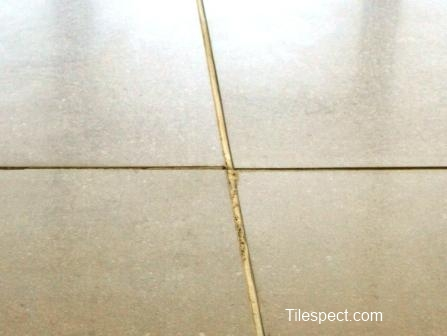 Faulty tiles? or good tiles laid over an uneven surface?What is happening in the joint?